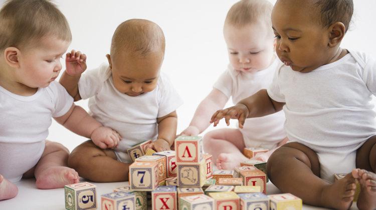 Cztery noworodki bawiące się kockami