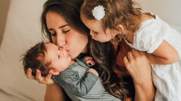 Kobieta ze starszą córką całują niemowlę