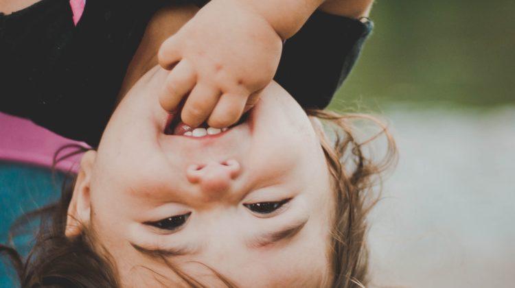 uśmiechnięta dziewczynka głową w dół