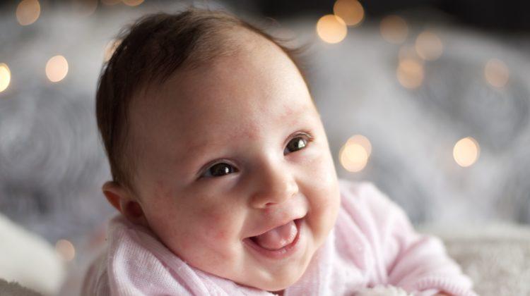 uśmiechnięty noworodek patrzący w górę